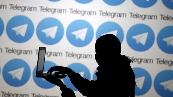 A man poses with a laptop in front of the Telegram logos in this picture illustration taken in Zenica